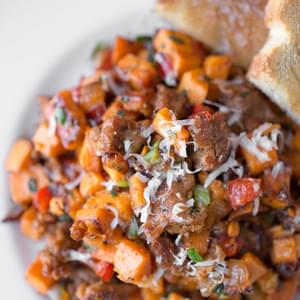 Autumn Sweet Potato Hash with Spicy Italian Sausage, Red Bell Peppers and Caramelized Onions, topped with a sprinkle of Fresh Herbs and Asiago Cheese